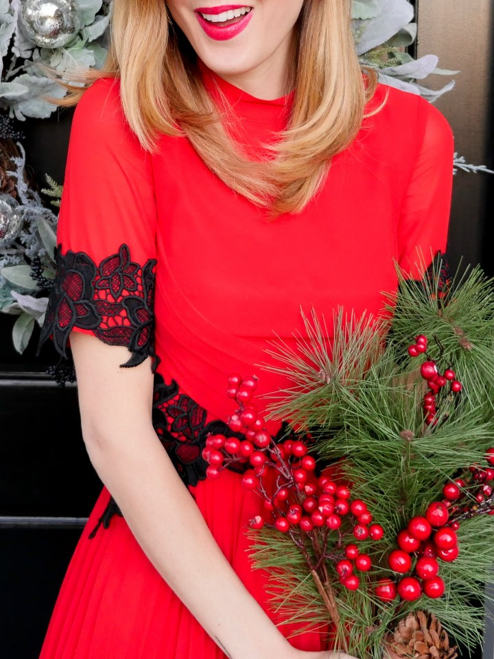Eva Amurri Martino wears a festive red dress with black lace detailing and holds a bunch of holly
