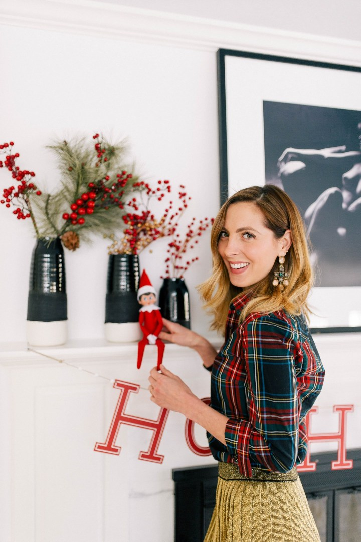 Eva Amurri Martino wears a plaid shirt and puts the Elf On The Shelf on the mantel in her kitchen