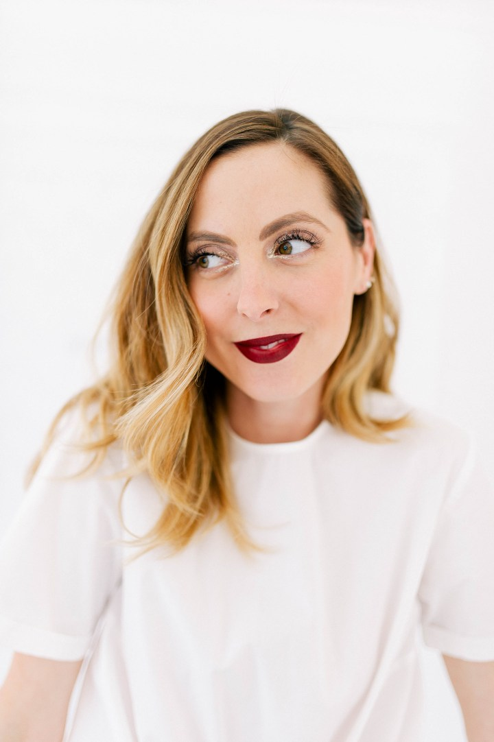 Eva Amurri Martino wears dark red lipstick and a hint of glitter eyeliner in the corners of her eyes for a fun and festive holiday makeup look