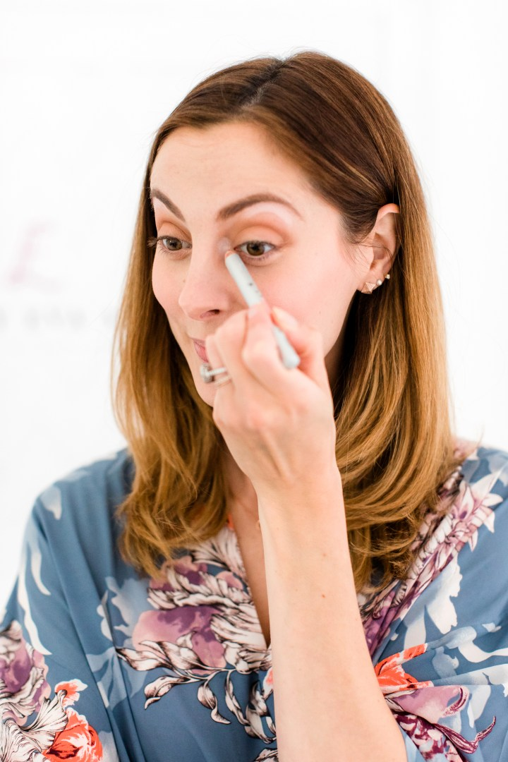 Eva Amurri Martino adds a highlighter stick to the inner corners of her eyes as part of a makeup tutorial