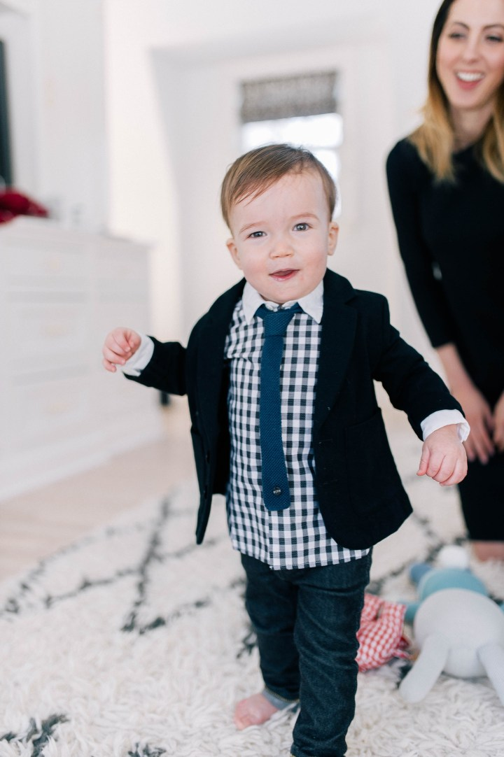 Major James Martino walking on the rug in his parents bedroom wearing a navy blue blazer and gingham shirt with a tie and jeans while his mother, Eva Amurri Martino, watches on from behind.