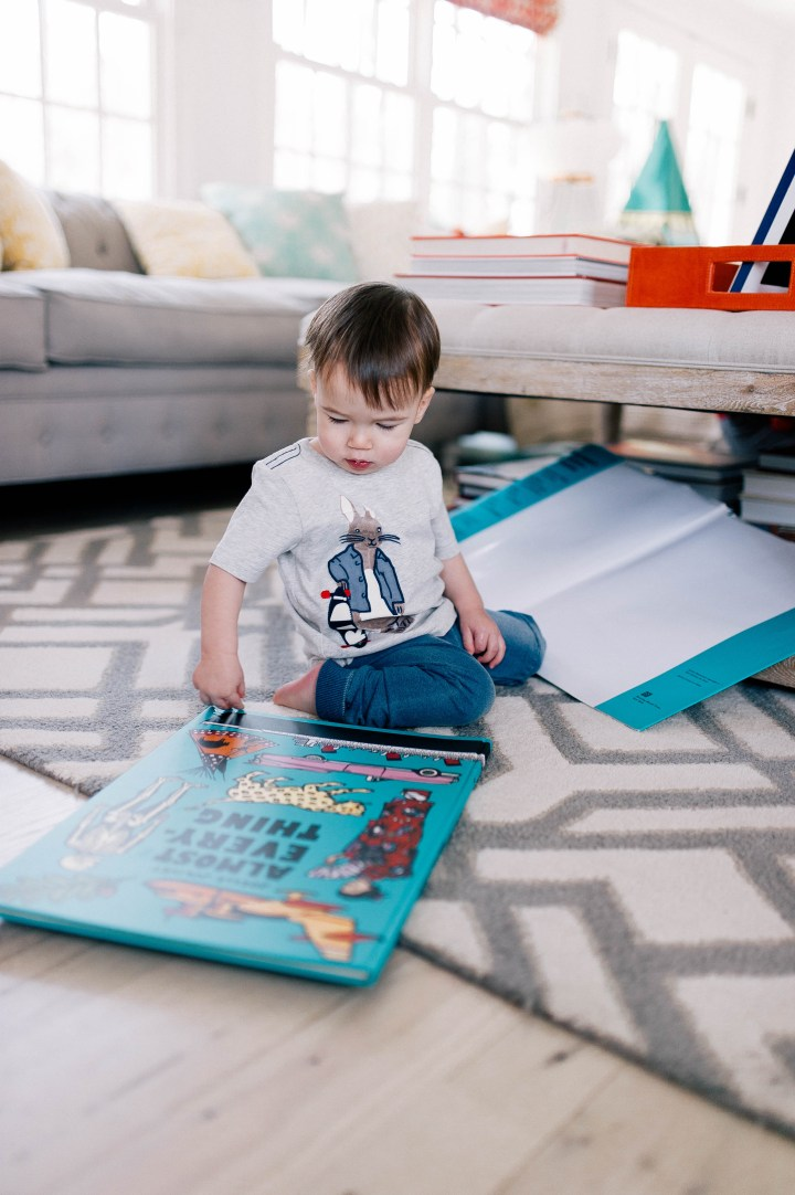 Major Martino wears a Peter Rabbit tee shirt and reads books on the floor of the family room