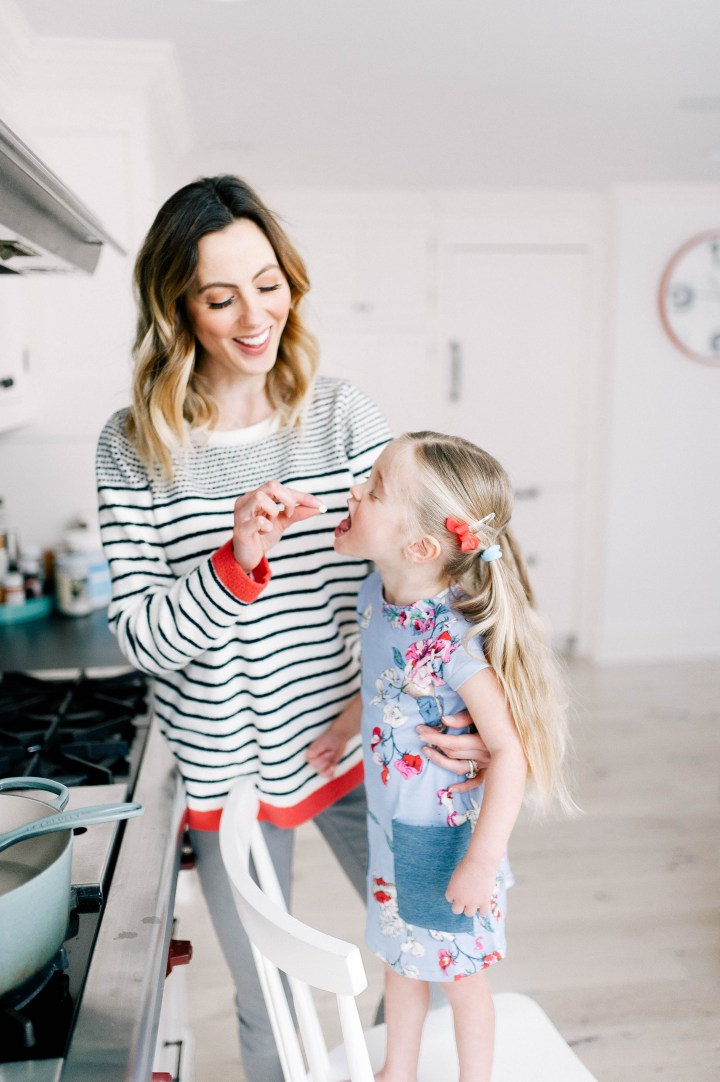 Eva Amurri Martino feeds daughter Marlowe a white chocolate chip while cooking in the kitchen at home