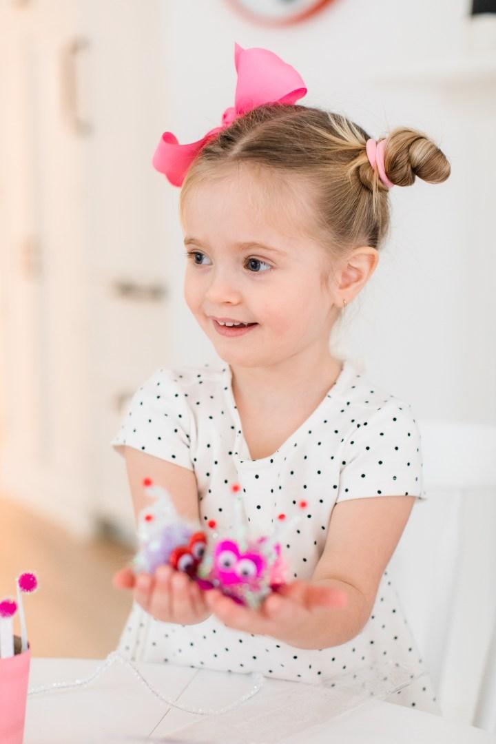 Marlowe Martino holds some cute DIY pompom Lovebugs