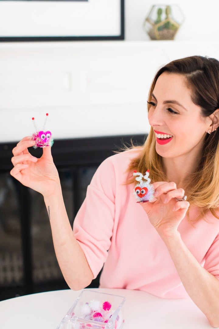 Eva Amurri Martino holds up two cute little DIY pompom Lovebugs as part of a Valentine's Day kid craft
