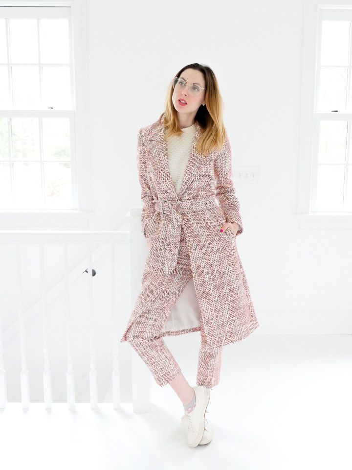 Eva Amurri Martino wears red and white patterned trousers, a matcing coat, and clear glasses in the studio of her Connecticut home