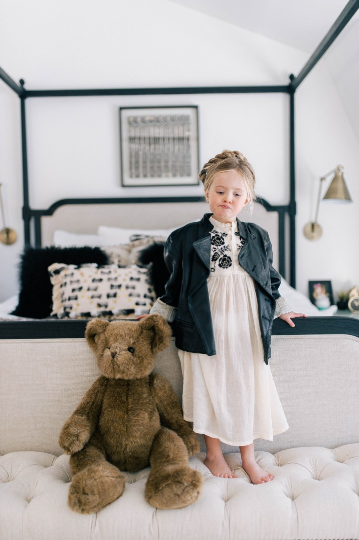 Marlowe Mae Martino pouting with a teddy bear, wearing an ivory tunic dress, leather jacket, and a halo braid in her parents bedroom in their Connecticut home.