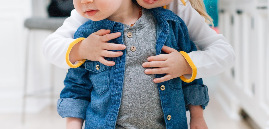 Stylish tot, Major Martino, wears a trendy denim button up over a grey t-shirt, while he gets a hug from older sister Marlowe.