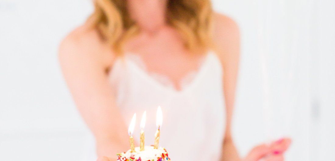 Eva Amurri Martino holds a cupcake with a candle to commemorate the 3rd birthday of her blog Happily Eva After