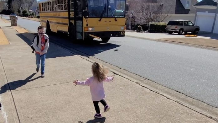 Girl runs to hug brother as he gets off school bus