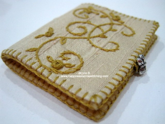 Embroidered needlebook, silk roses stitched on linen finished with a blanket stitch around the edge