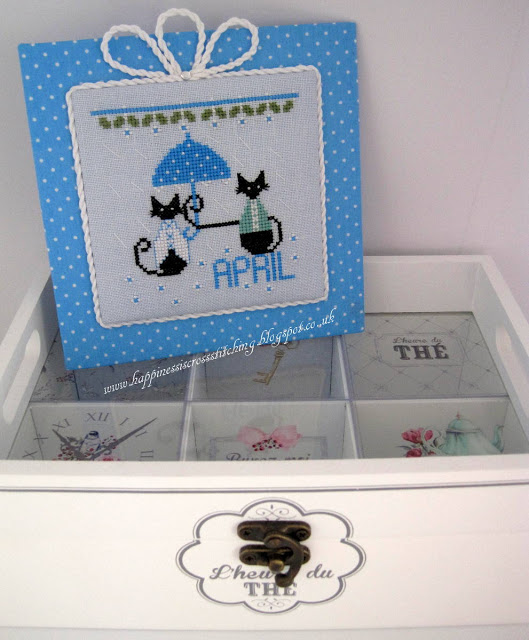 Cross stitched pattern showing two mini black cats, one holding an umbrella and the other being protected from the rain. Stitched in pretty blu threads with matching background polka dot fabric.