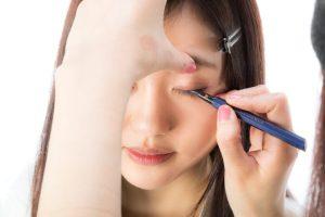 甲状腺機能低下症の女性が化粧でアイライナーを使っているイメージ