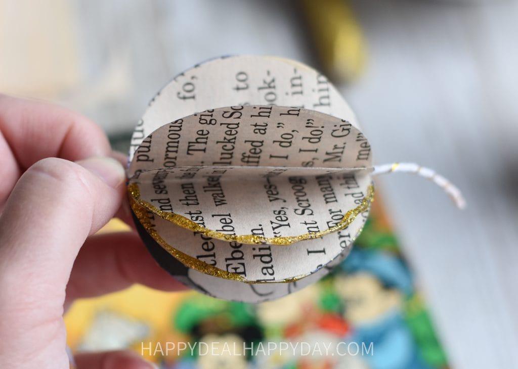 Adding glitter to thrift store books Christmas ornament