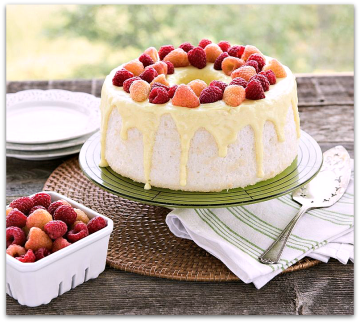 Angel food cake, white with yellow drizzle and strawberries