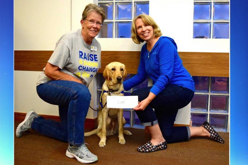 Canine Companions for Independence Kansas City chapter puppy raiser kneeling by dog in training and accepting donation check from Happy-Go-Doodle founder who won a donation to non-profit as part of BlogPaws Best New Pet Blog win