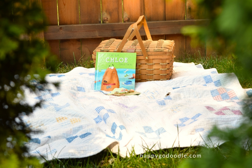 I See Me Personalized book leaning against a picnic basket sitting on a quilt on green grass