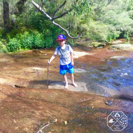 Kid playing at Somersby Falls waterfalls
