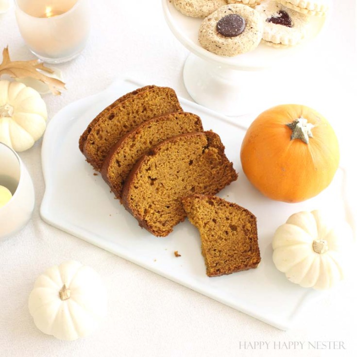 slices of pumpkin bread on a white platter with pumpkin surrounding it