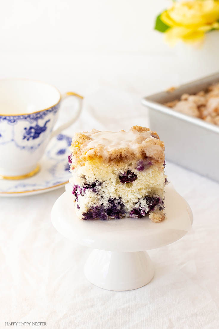 Blueberry cakes are so delicious. This dessert is The Best Blueberry Buckle Cake Recipe and is sure the perfect side to a cup of coffee or tea. Serve it as a dessert or as a morning blueberry coffee cake. This easy recipe makes an impressive cake with the crumble and delicious icing. #cake #coffeecake #blueberrydessserts #blueberries #desserts #pastry