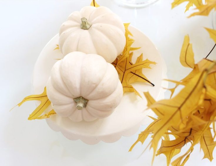 two white mini pumpkins on a cake stand with yellow leaves