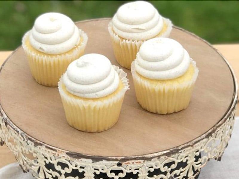4 lemon cupcakes on white cakestand