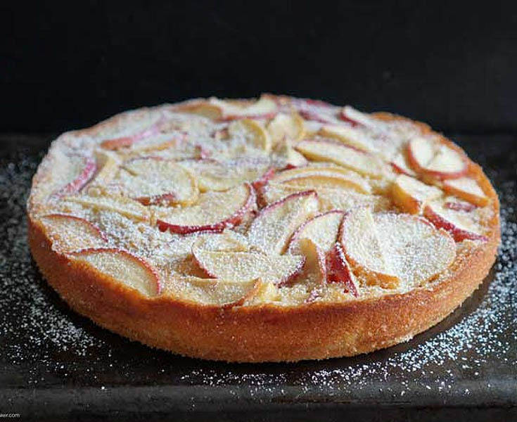 whole apple tart with powdered sugar sprinkled on top. Tart is placed on a black table top