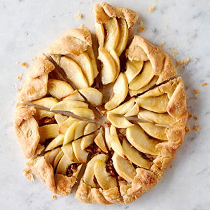 rustic apple tart with crumbs on a marble countertop