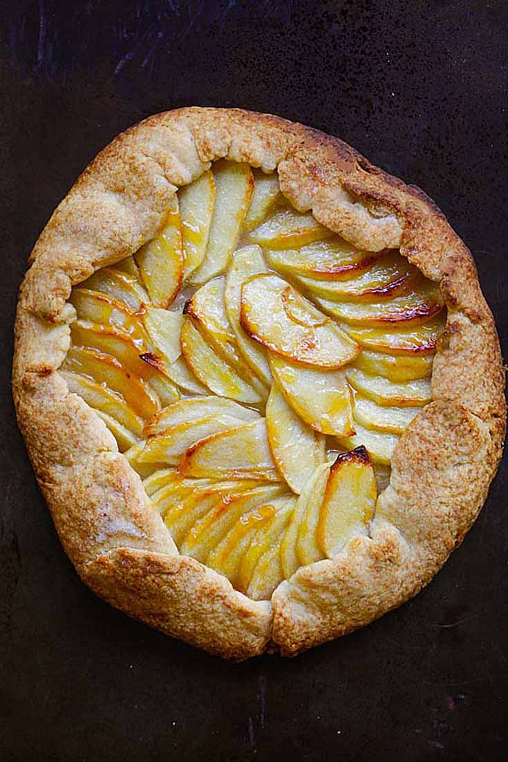 rustic apple tart with outer crust. Tart is on a black background