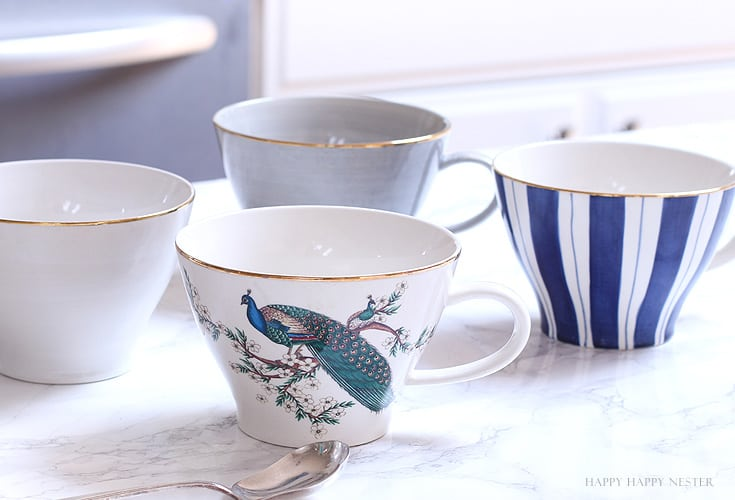 four mugs on a counter top in a kitchen