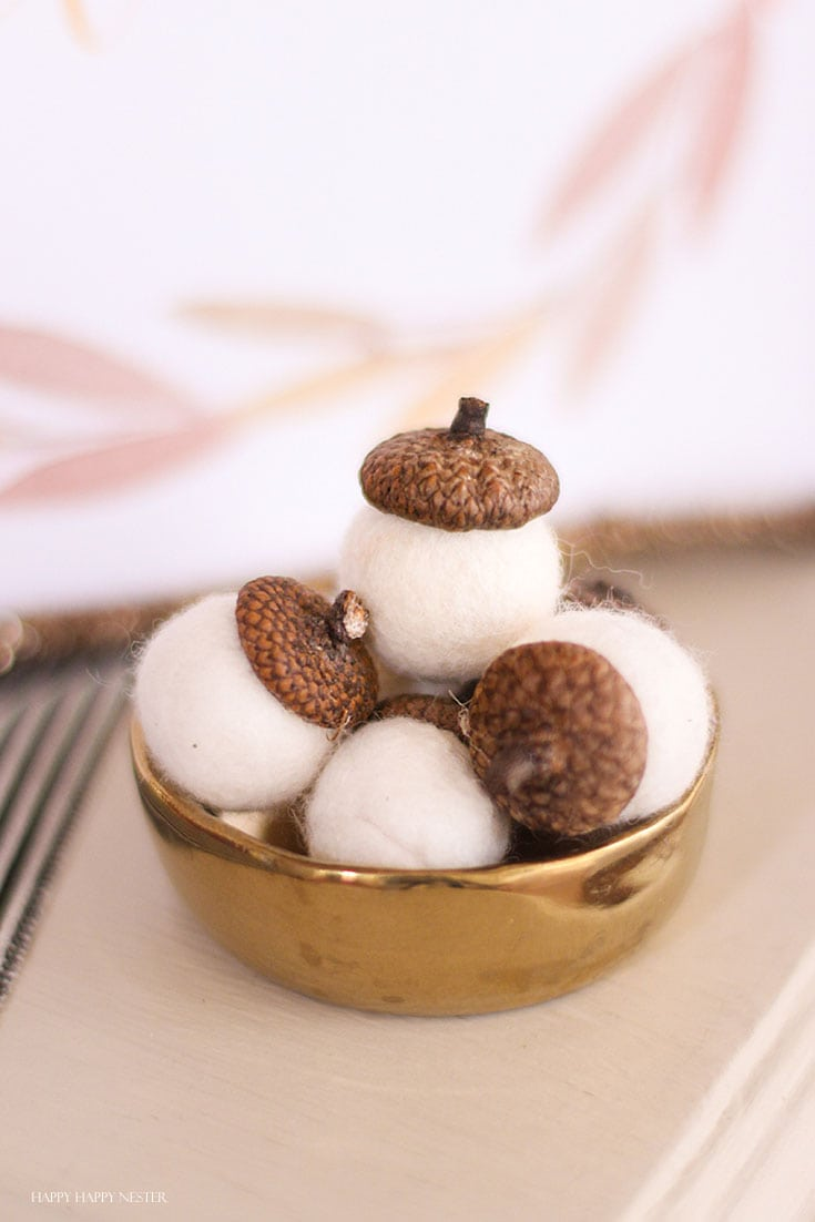 wool white acorns in a gold bowl