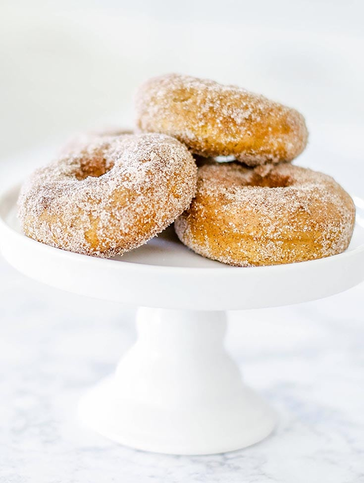three cinnamon donuts on a white cake stand