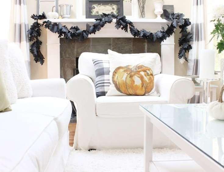 white living room with black leaf garland on mantel