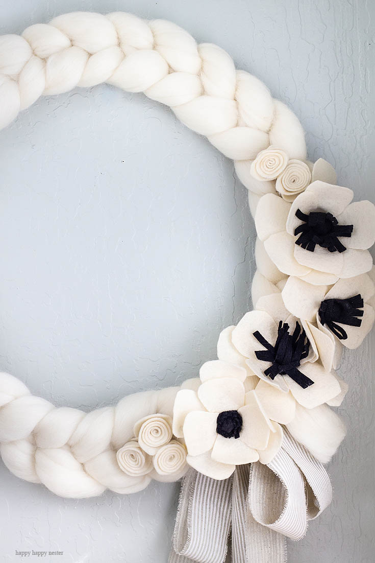This white wreath is the perfect thing to brighten your home. Here is a quick and easy arm knitted wreath to chase your winter blues away! This wreath is so easy to arm knit, and you'll seriously love the results. I love how this bright wreath will look great all year long. Crafts | Arm Knit | Arm Knit Wreath | Wreaths | Wreath DIY | Craft Tutorial | Arm Knit Project | Wreath