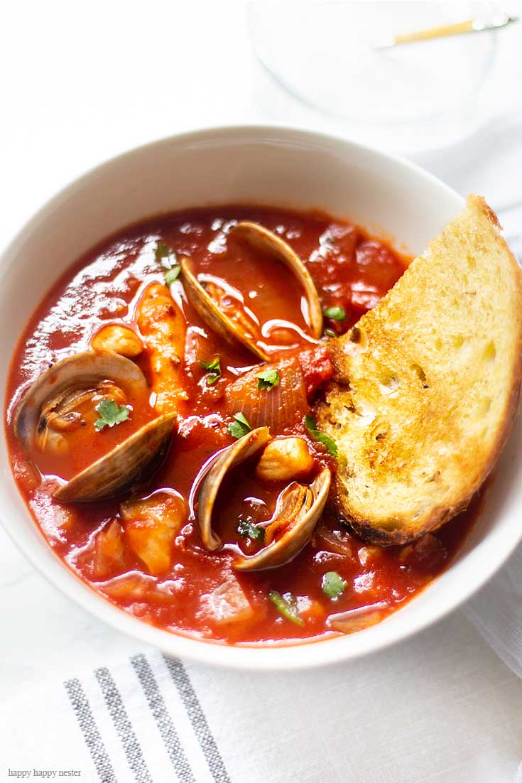 For a cold winter night or a warm summer dinner, this Cioppino is a perfect meal. Our family favorite Yummy Seafood Stew Recipe is the best San Francisco style Cioppino. Make this the evening before so all the flavors are their best. This is the best Cioppino recipe since it includes wine and sugar to balance and mellow the acid from the tomatoes. #cioppino #italiandinner #soup #fishstew