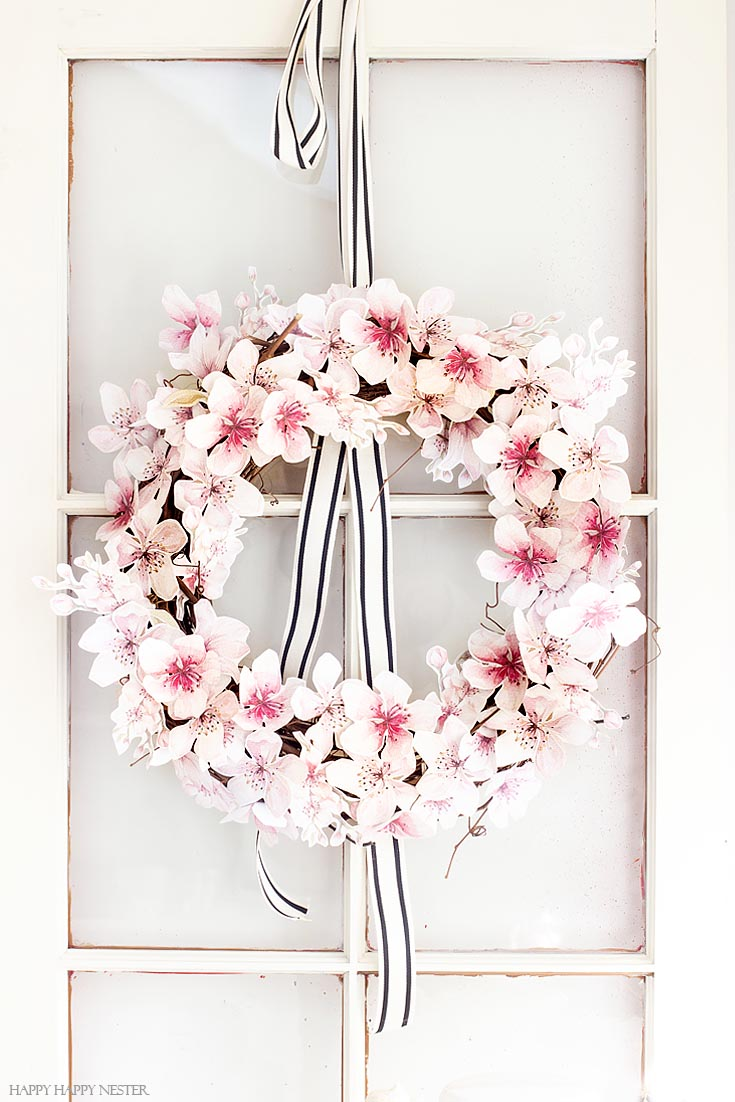 Make this floral paper wreath. This easy How to Make a Paper Flower Wreath DIY is perfect for the spring. This wreath uses watercolor cherry blossoms that you cut out and glue to a grapevine wreath. It is a simple wreath that is beautiful and nice year round. The supplies include a wreath, paper, scissors, glue, and ribbon. #crafts #wreaths #spring