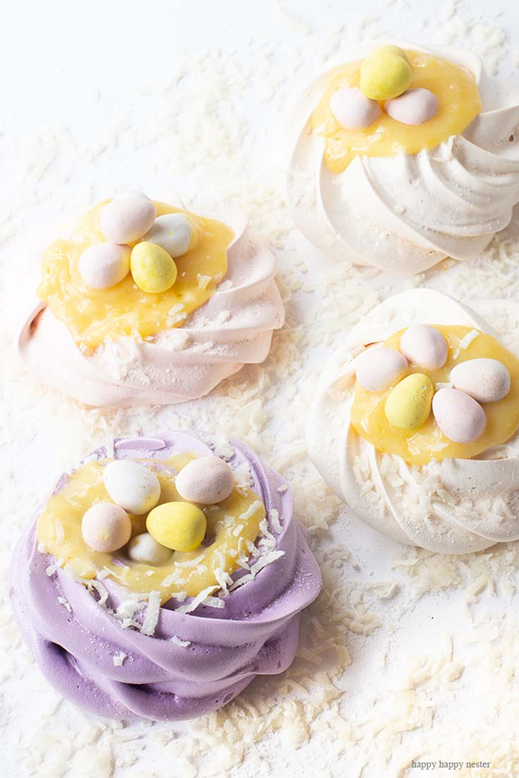 Love these easy and adorable pavlova nests. This Pavlova Recipe is so easy and the Mini Nests are so adorable. They are perfect for Easter, a spring dessert or year-round treat. Use different food colors to create cute fresh nests. Top the nests with lemon curd, whip cream, and Easter eggs. #baking #easter #desserts #easterdesserts #meringue #pavlova #lemoncurd
