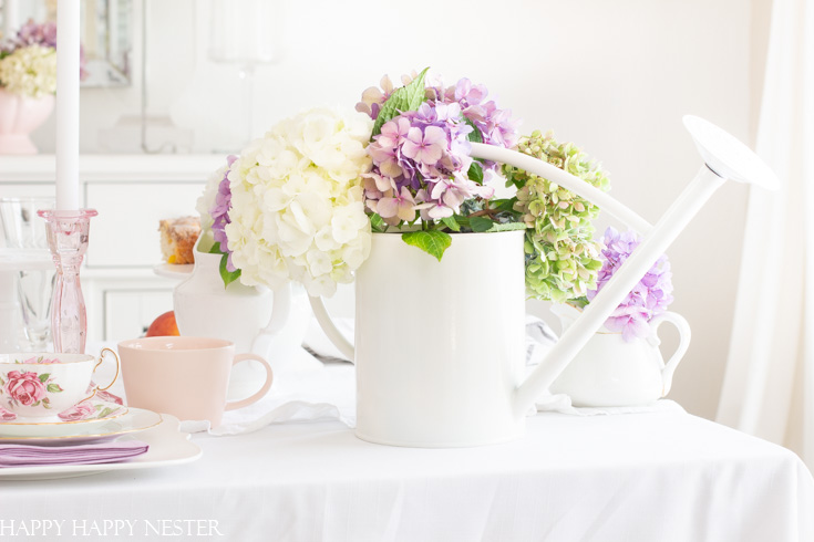 Create a gorgeous summer table decor with hydrangeas in just a few minutes. These summer garden flowers are the perfect addition to an easy summer table. Add a few white water cans as vases, and you have a fresh cute table decor. #summertable #hydrangeas #decor