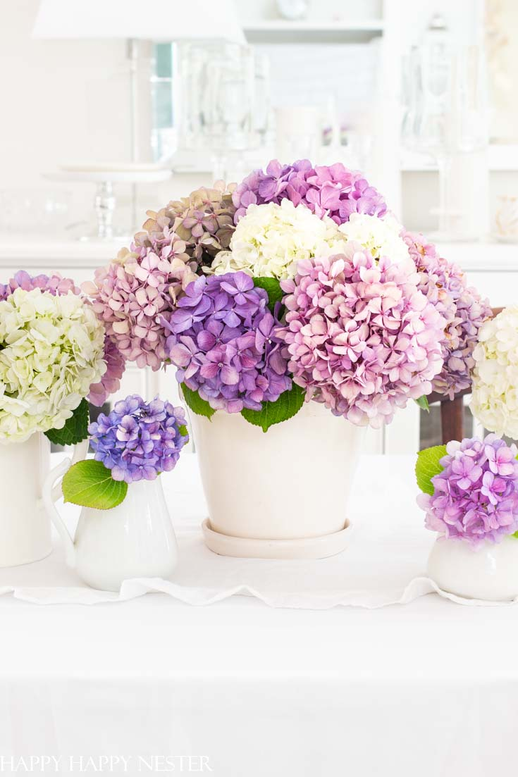 Create a gorgeous summer table decor with hydrangeas in just a few minutes. These summer garden flowers are the perfect addition to an easy summer table. Add a few white vases, white table cloth, and you have the perfect canvas to add your colorful hydrangeas. #summertable #hydrangeas #decor