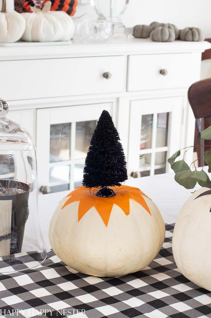 This cute tissue paper pumpkin craft is so easy. You can tack it down with glue or modge podge it to the pumpkin. Top with a cute Halloween bottle brush tree. #halloween #modgepodge #crafts #halloweencrafts #pumpkinideas
