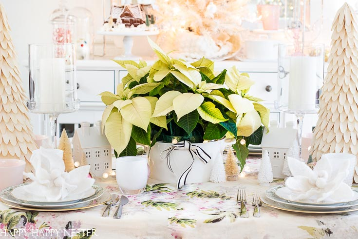 Use white Christmas poinsettias on your holiday tables. Find out these table ideas for Christmas decorating. This table decor is feminine and vintage all rolled up in one. #shabbychic #Christmasvintage #vintageornaments #whitepointsettias