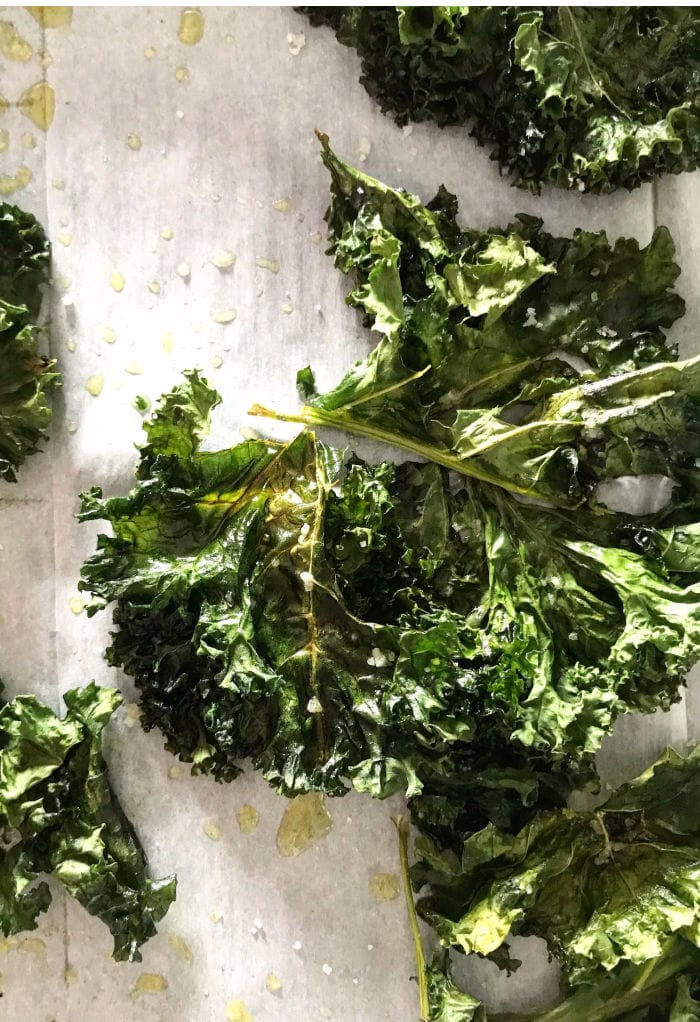 crispy kale on a white board with drops of oil