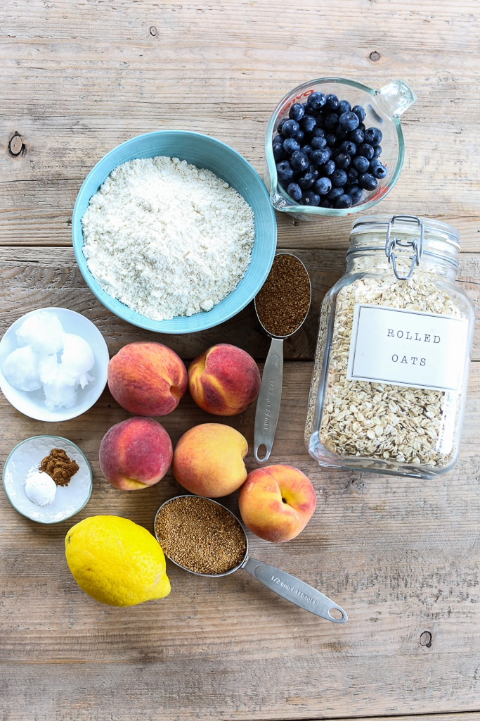 overhead shot of ingredients for healthy crisp recipe. Peaches blueberries flour oatmeal lemon coconut oil sugar