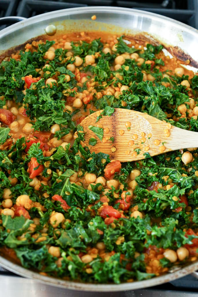 stirring in kale and chickpeas with a wooden spoon