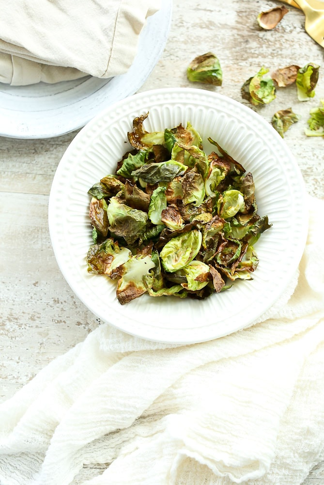 Crispy Brussels Sprouts Chips on the table in a bowlCrispy Brussels Sprouts Chips on the table in a bowl