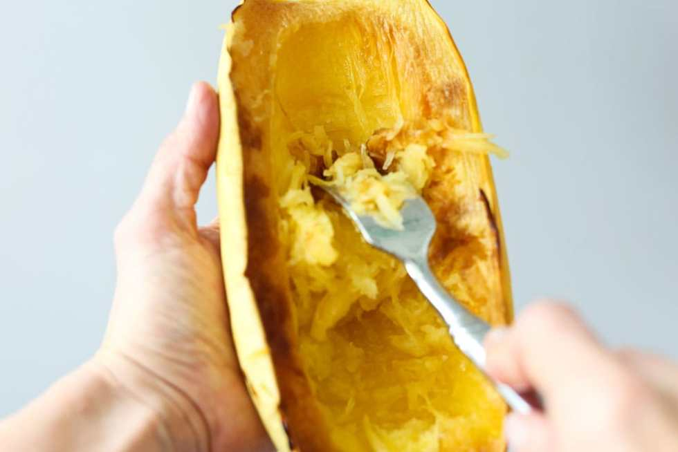Removing the strands of cooked spaghetti squash for the mediterranean spaghetti squash with chicken and spinach recipe