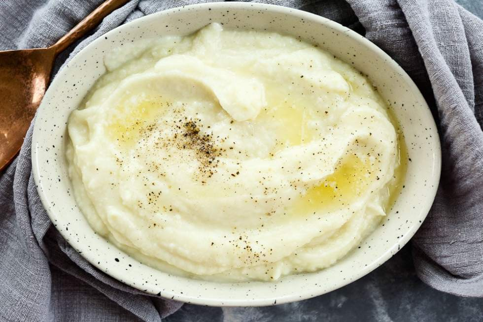 Instant Pot Mashed Cauliflower Recipe--in a bowl with melted butter and a copper serving spoon