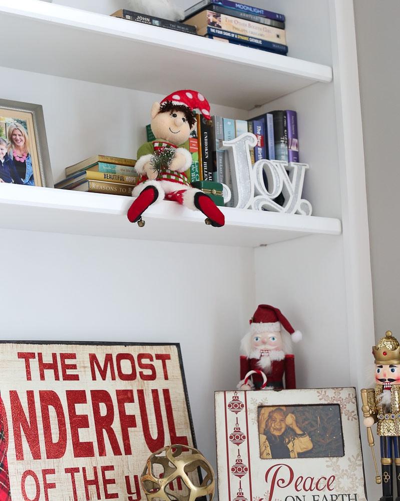 Dingle the original elf on the shelf-sitting on a bookshelf