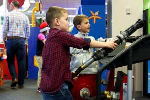 Luke's 6th Birthday Party at Chuck E Cheese's-playing the fire fighting game