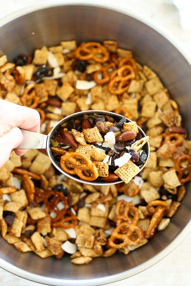 Sweet and Salty Chex Mix Recipe scooping out of a big bowl